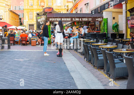 Young people congregate at the Cours Saleya Old Town area in Nice, France as diners enjoy an early dinner on the French Riviera. - Stock Photo