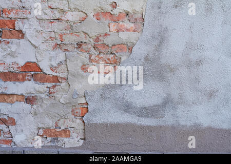 Old weathered red brick wall fragment, crumbling plaster