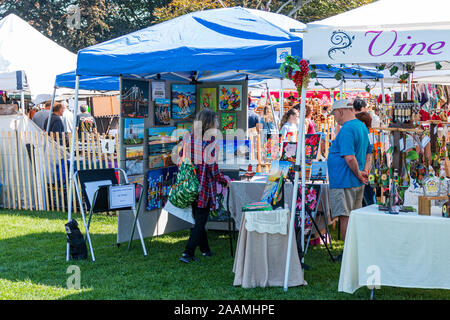 West Islip, New York, USA - 22 September 2019: People shopping and asking questions to the vendors at the annual West Islip goods fair. - Stock Photo