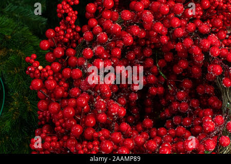 Holly berries with pieces of ice, New Year Christmas scenery. Red artificial holly berries braided in a wreath. Backdrop wallpaper background - Stock Photo