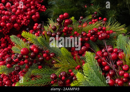 Holly berries and Christmas tree. New Year Christmas decoration, backdrop background. Artificial Christmas tree and decorative red berries of holly - Stock Photo
