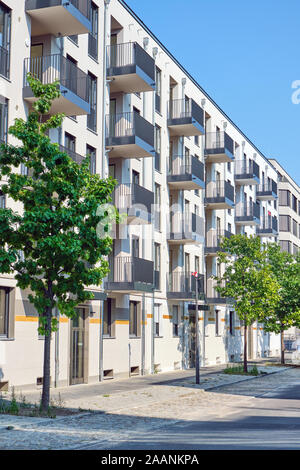 Street with new apartment buildings seen in Berlin, Germany - Stock Photo