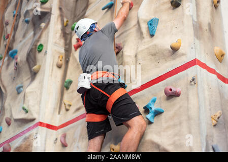 Sporty man practicing indoor rock climbing in climbing gym . - Stock Photo