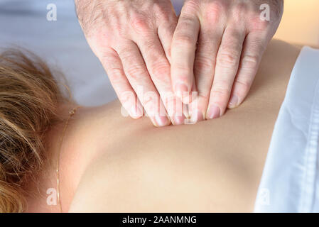 Close-up on the man doctor hands. Caucasian Woman Receiving Therapeutic Back Massage in medical office. A young girl receives a body massage in a spa salon from a male masseuse. - Stock Photo