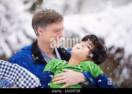 Smiling father holding disabled young son in his arms  outdoors during snowfal. Child has cerebral palsy - Stock Photo