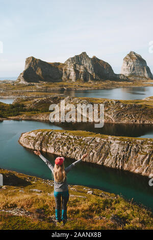 Woman adventurer raised hands traveling in Norway mountains rocks and sea view adventure vacations healthy lifestyle success motivation Helgeland isla - Stock Photo
