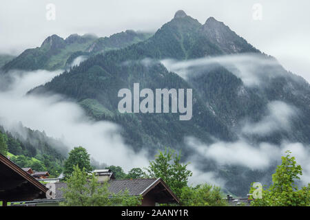 Low early morning clouds floating in the valleys of the mountains around Fusch an der Grossglocknerstrasse - Stock Photo