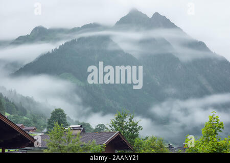 Low morning clouds and haze floating in the valleys of the mountains around Fusch an der Grossglocknerstrasse - Stock Photo