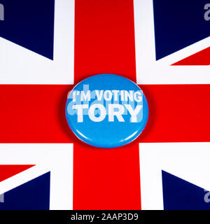 London, UK - November 21st 2019: I'm Voting Tory pin badge, pictured over the United Kingdom flag. The UK General Election is taking place on 12th Dec - Stock Photo