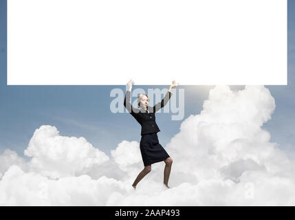 Beautiful woman in suit standing near banner - Stock Photo