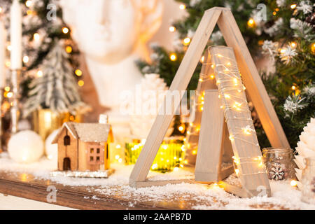 Closeup of wooden pyramid wrapped in garland standing next to little wooden house. - Stock Photo