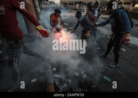 Baghdad, Iraq. 23rd Nov, 2019. Iraqi protester extinguish a burning projectile during a violent anti-government protest. Credit: Ameer Al Mohammedaw/dpa Credit: dpa picture alliance/Alamy Live News/dpa/Alamy Live News - Stock Photo