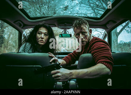 Two people, a male and female appear in danger or maybe they are the dangerous ones? they are sat in a car covers in dirt and weapon in hand - Stock Photo