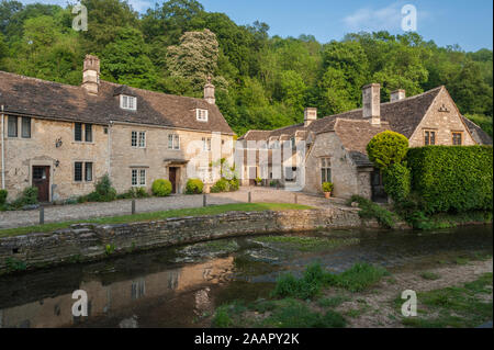 CASTLE COMBE, COTSWOLDS, UK - MAY 26, 2018: Street view of old riverside cottages in the picturesque Castle Combe Village, Cotswolds, Wiltshire, UK - Stock Photo