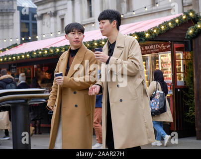 Two asian young man in trenchcoats drinking hot chocolate from Christmas market stall at Trafalgar Square - Stock Photo