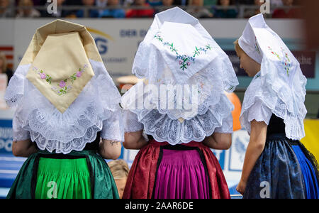 Cottbus, Germany. 23rd Nov, 2019. Gymnastics: World Cup, 44th International Tournament of Champions, Final: Flower girls in Serbian costume are waiting for the award ceremony. Credit: Monika Skolimowska/dpa-Zentralbild/dpa/Alamy Live News - Stock Photo