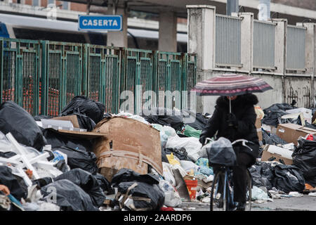 Caserta, Italy, February 21, 2008: A woman on a bicycle passes by waste accumulating on a street in Caserta, Italy, north of Naples during the Naples waste management crisis in 2008. - Stock Photo
