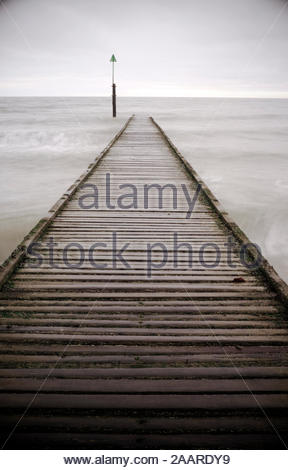 Narrow wooden walkway leading in to a grey sea. - Stock Photo