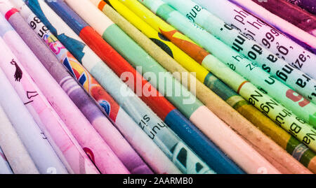 Colourful book covers lined up on a shelf in a study - Stock Photo