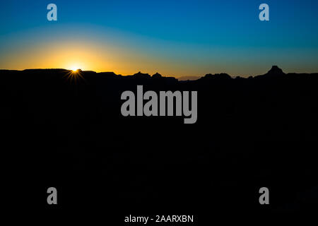 Orange sun rising over dark desert canyon with jagged peaks, mesas and towers silhoutted against the blue sky. - Stock Photo
