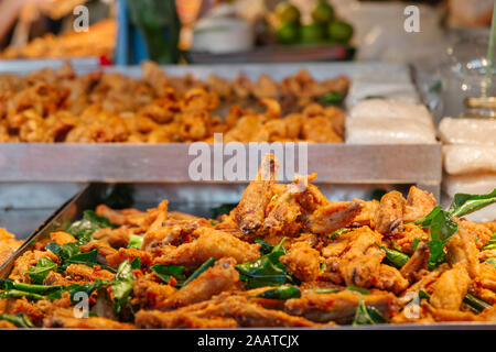Heap of Thai style deep fried crispy chicken wings for sale in the local street food market in Bangkok, Thailand. - Stock Photo