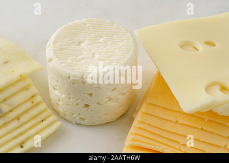 Variety of cheese close up. Brie, or camembert, pepper jack, gouda, and swiss cheese sliced on a marble serving board. - Stock Photo