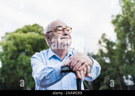Portrait of senior man in a park leaning on his walking stick - Stock Photo
