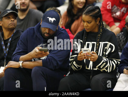 San Diego, California, USA. 23rd Nov, 2019. Retired 13-time NBA All-Star Dwyane Wade, left, and his wife Gabrielle Union-Wade look at their phones during a break in the action of a Sierra Canyon basketball game against Cathedral Catholic. Wade's son Zaire Wade and Lebron James son LeBron James Jr., (Bronny) play for Sierra Canyon. Credit: KC Alfred/ZUMA Wire/Alamy Live News - Stock Photo