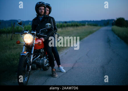 Portrait of young couple on vintage motorbike at roadside - Stock Photo
