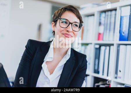 Portait of smiling young businesswoman in office - Stock Photo