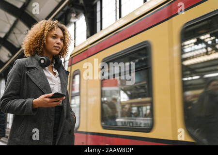 Woman with cell phone in subway station as the train comes in - Stock Photo