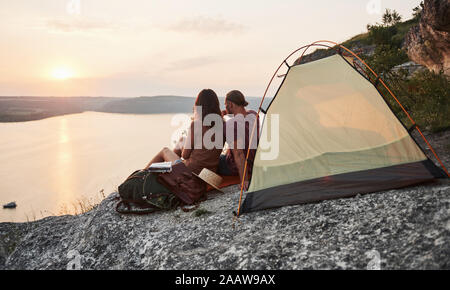 Photo of happy couple sitting in tent with a view of lake during hiking trip. Travel Lifestyle adventure vacations concept Stock Photo