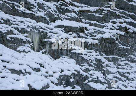 A lot of icicles have been formed due to the water rushing down the mountains and then freezing while falling down a cliff. - Stock Photo