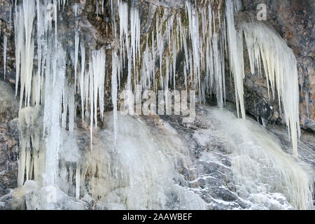 Frozen waterfall with a lot of icicles, that have been formed due to the water rushing down the mountains and then freezing while falling down a cliff - Stock Photo