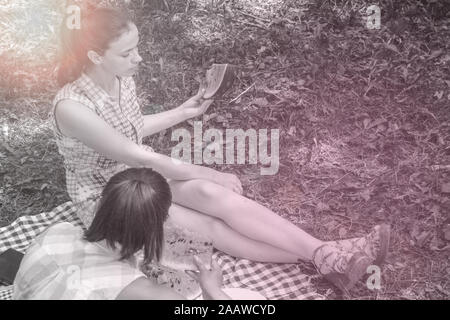 Two young women enjoying  conversation and eating watermelon on picnic outdoors - Stock Photo