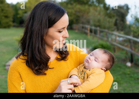 Mother holding sleeping baby girl in her arms - Stock Photo