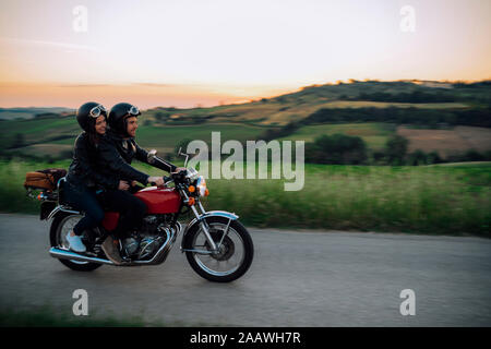 Young couple riding vintage motorbike on country road at sunset, Tuscany, Italy - Stock Photo
