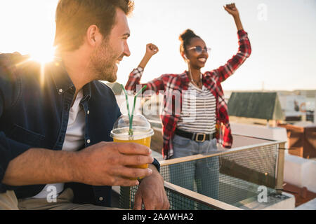 Happy young couple having a rooftop party at sunset - Stock Photo