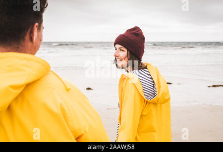 Young woman wearing yellow rain jackets and walking along the beach, Bretagne, France - Stock Photo