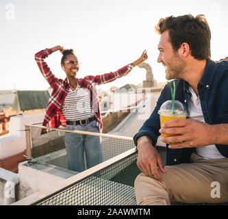 Happy young couple having a rooftop party - Stock Photo