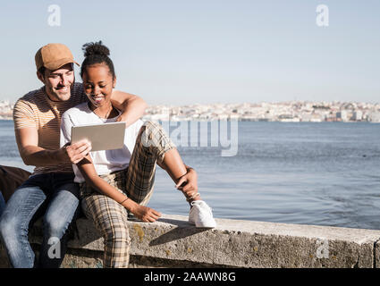 Happy young couple sitting on a wall at the waterfront using a tablet, Lisbon, Portugal - Stock Photo