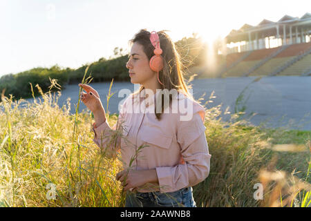 Young woman listening music with headphones outdoors - Stock Photo