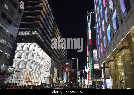 Buildings in Ginza district at night, a popular upscale shopping area in Tokyo, Japan - Stock Photo