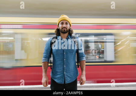 Portrait of bearded man standing at platform in front of driving commuter line, Berlin, Germany - Stock Photo