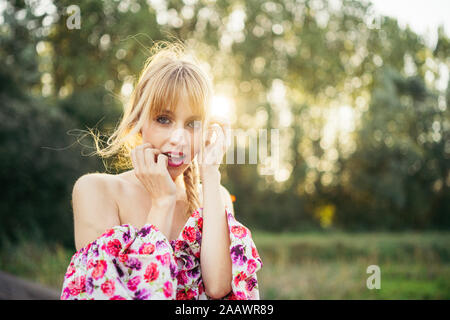Portrait of blond young woman wearing summer dress with floral design at backlight