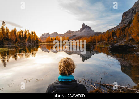 Female hiker looking at the mountain landscape with lake at the first light of the day, Dolomites Alps, Cortina, Italy - Stock Photo