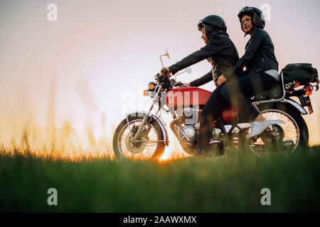 Young couple on vintage motorbike at sunset - Stock Photo