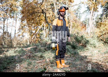 Full length portrait of a professional lumberjack in protective workwear standing with a chainsaw in the forest - Stock Photo