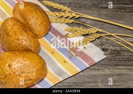 Rustic still life with bread buns, grains and ears of wheat on a wooden table - Stock Photo