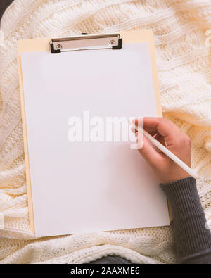 Woman hand with pen writing Christmas greetings on clipboard - Stock Photo